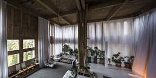 A Spanish Architect Converts a Cement Factory Into a Breathtaking Home and Headquarters - Photo 8 of 12 - The voluminous living room has plenty of windows, letting in an abundance of natural light.
