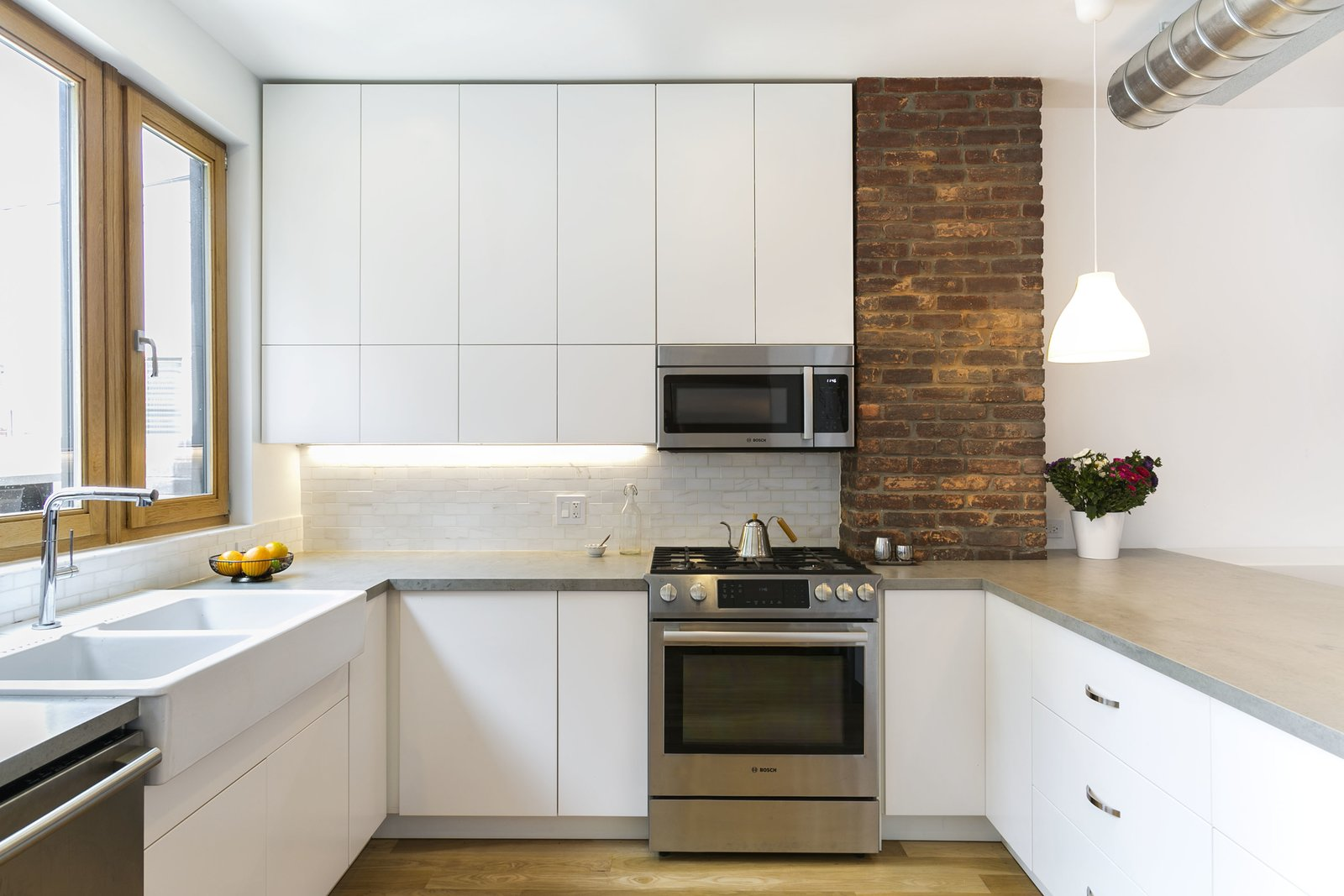 Another view of the kitchen. Tagged: Kitchen, Engineered Quartz Counter, White Cabinet, Ceramic Tile Backsplashe, Pendant Lighting, Light Hardwood Floor, Accent Lighting, Ceiling Lighting, Microwave, Range, and Dishwasher. Sunset Park Row House by Ula Bochinska