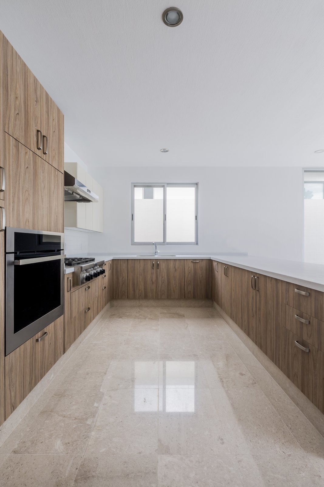Tagged: Kitchen, Wood Cabinet, Wood Counter, Marble Floor, Quartzite Counter, Ceramic Tile Backsplashe, Ceiling Lighting, and Wall Oven. CASA VALLE by Sergio Villalobos