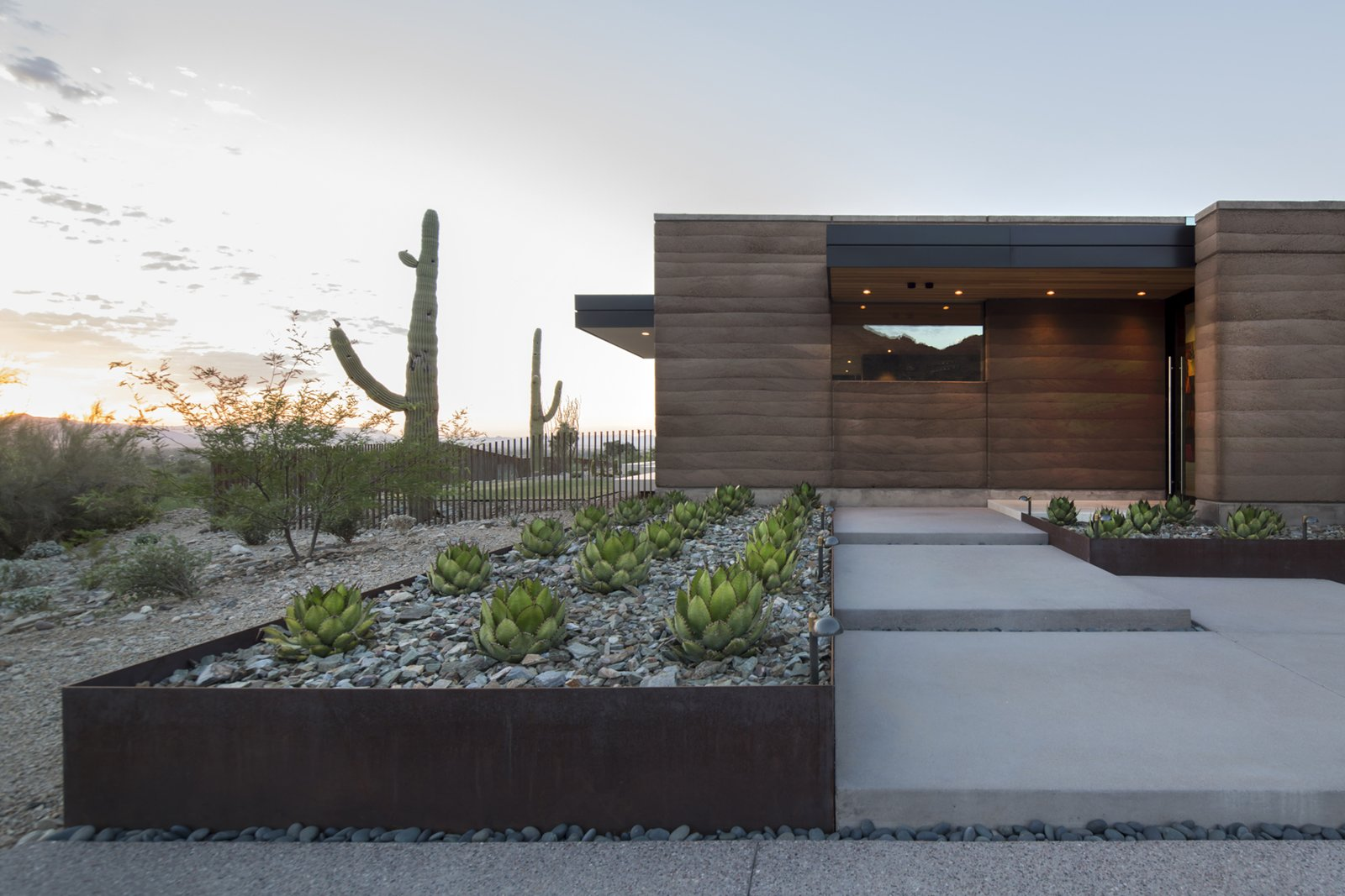 Tagged: Front Yard, Desert, Hardscapes, Trees, Raised Planters, Gardens, Walkways, Vertical, Metal, Landscape, Exterior, Wood, and House.  Best Exterior Gardens Metal Photos from Rammed Earth Modern