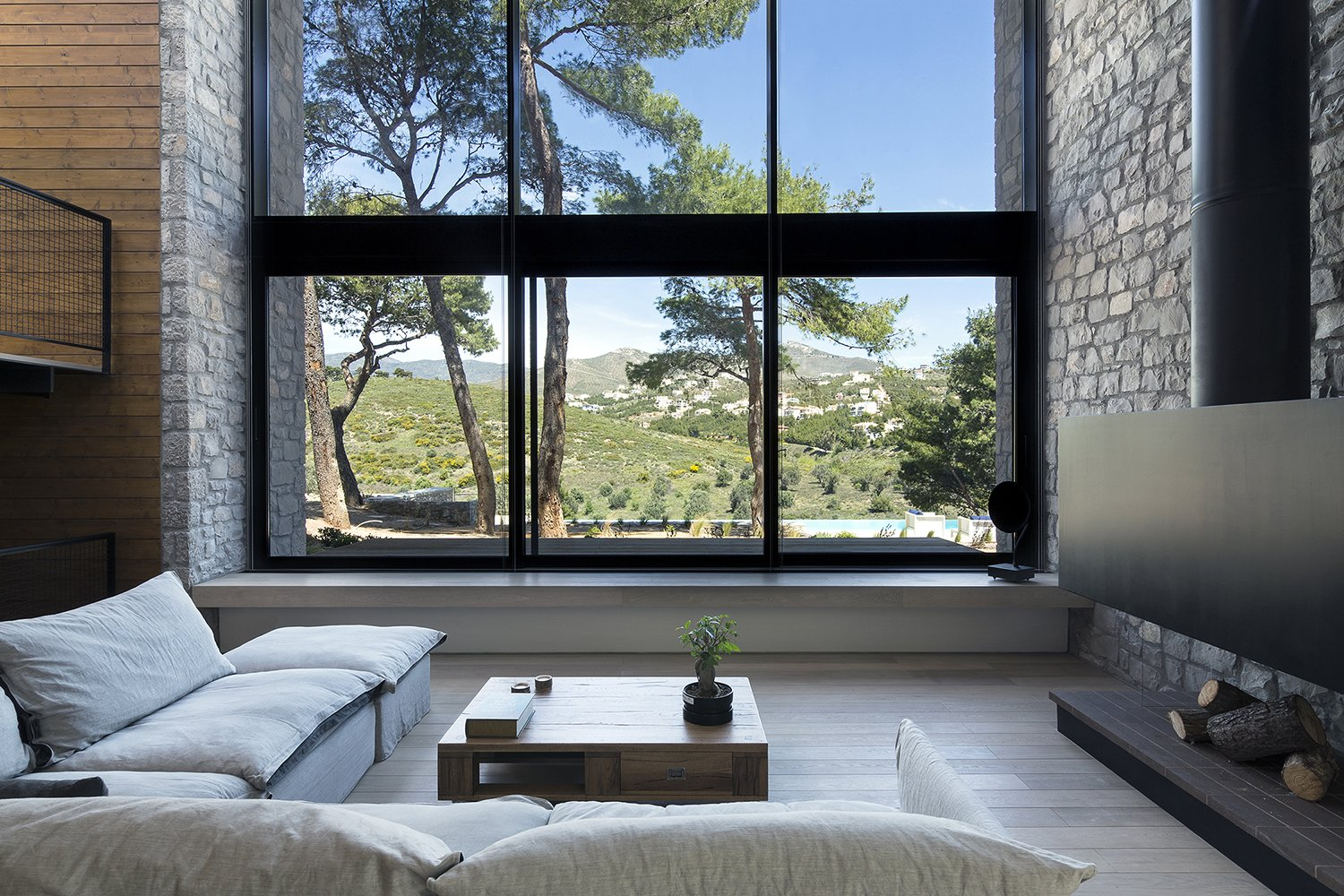 The facade opens up to the view of the pines trees concealing the boundary between the interior of the house and its surrounding environment  Tagged: Living Room.  The Wedge House by Marianna Athanasiadou
