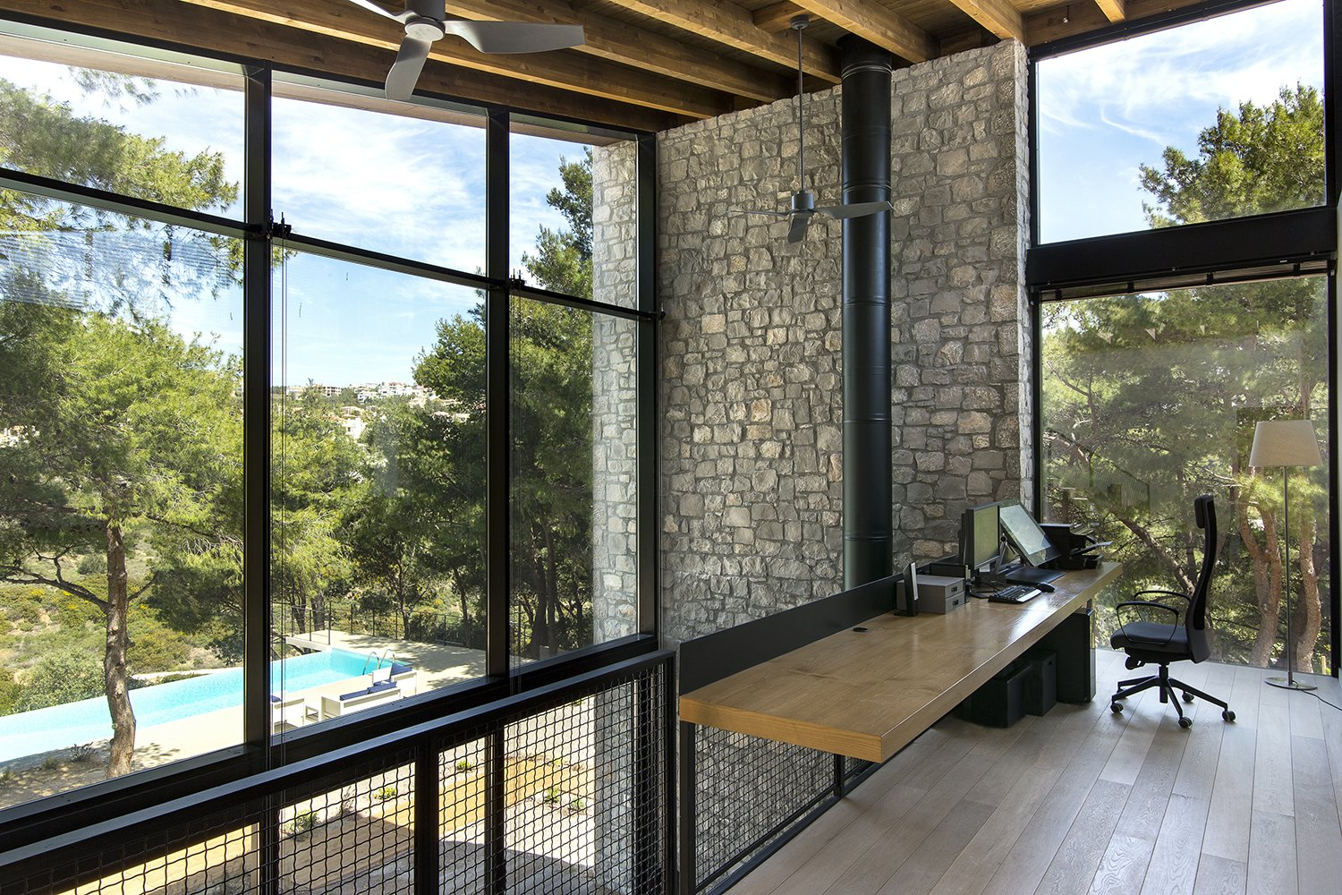 The facades open up to the view of the pines trees Tagged: Office, Study, Light Hardwood Floor, and Chair.  The Wedge House by Marianna Athanasiadou