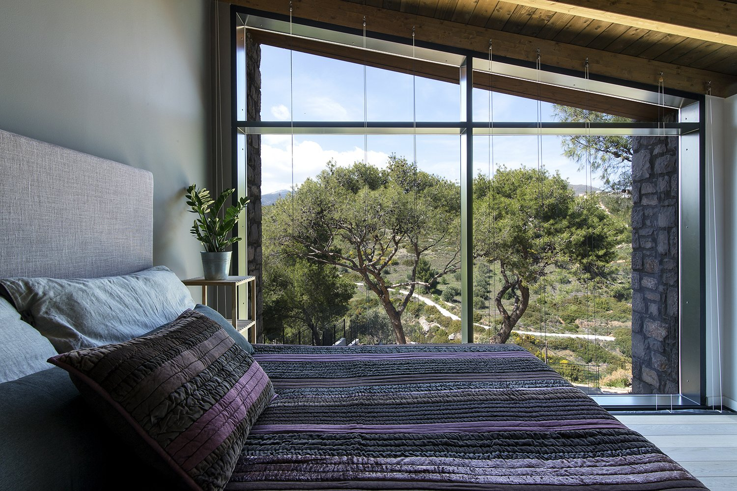 The facade opens up to the view of the pines trees concealing the boundary between the interior of the house and its surrounding environment  Tagged: Bedroom.  The Wedge House by Marianna Athanasiadou