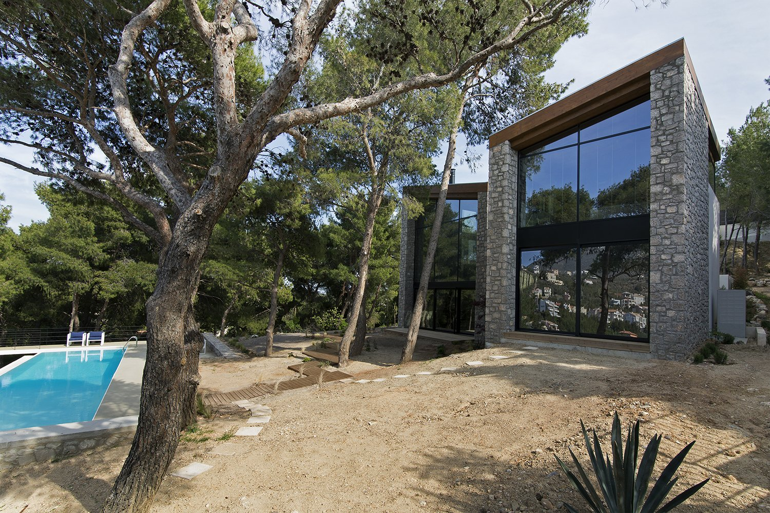 Both facades completely open up through large glazing surfaces to the view of the pines trees and the hills beyond Tagged: Exterior, Stone Siding Material, Shingles Roof Material, House, and Wood Siding Material.  The Wedge House by Marianna Athanasiadou