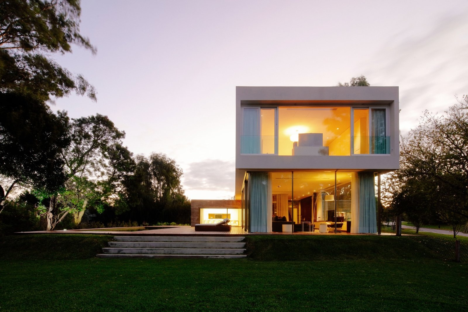 Side view of the House at Los Cisnes at dawn. Concrete, Glass, Wood. Tagged: Outdoor, Large Patio, Porch, Deck, Grass, Back Yard, Trees, and Wood Patio, Porch, Deck.  House at Los Cisnes by Esteban Fallone