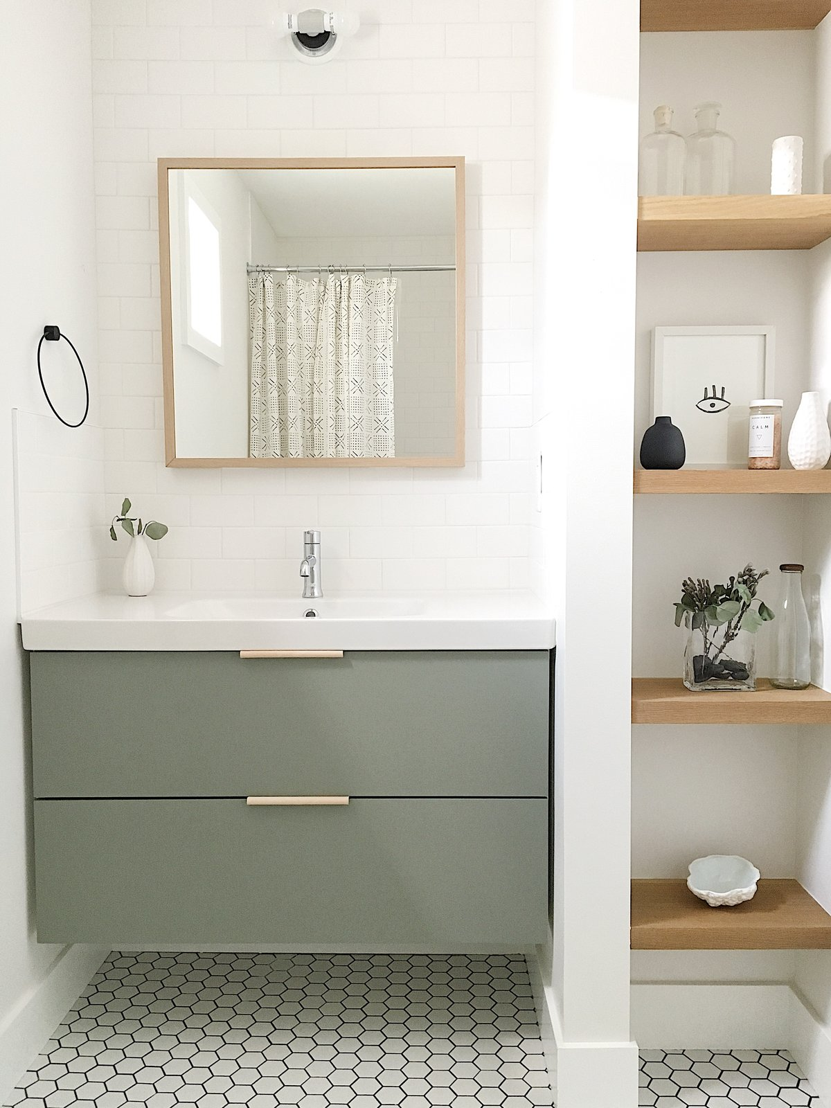 The guest bathroom utilizes a simple Ikea vanity custom painted to the perfect shade of green and features leather hardware from the Australian company Made Measure. Tagged: Bath Room, Wall Lighting, Porcelain Tile Floor, and Subway Tile Wall.  Best Photos from The Simply Simple Home