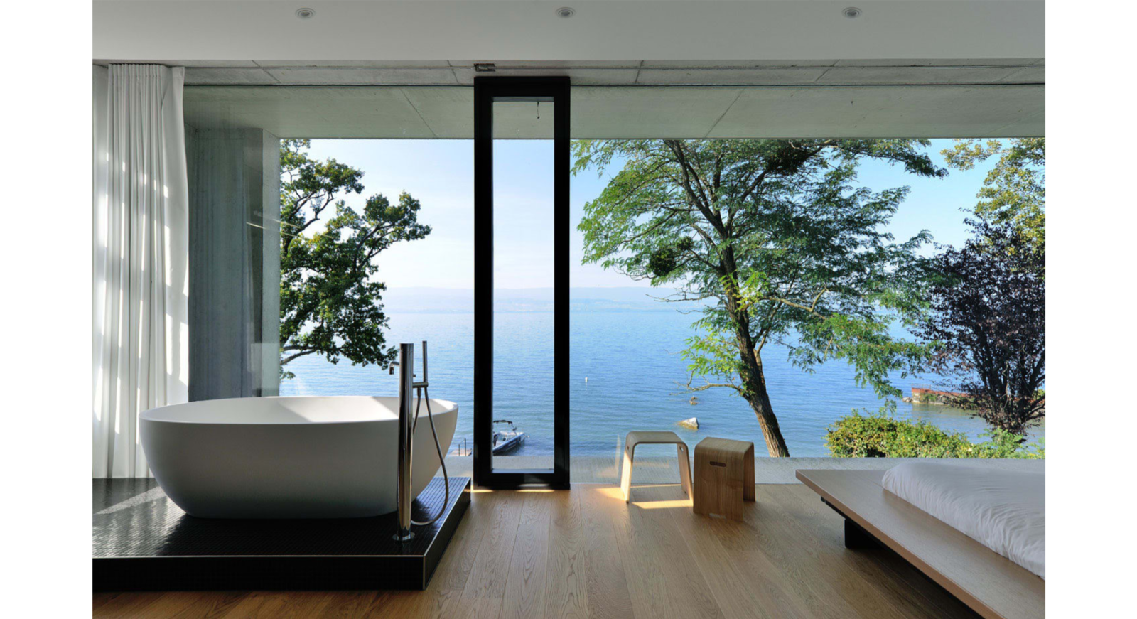 The bathroom Tagged: Light Hardwood Floor, Bed, Chair, Ceiling Lighting, Freestanding Tub, Concrete Wall, Tile Counter, Windows, Sliding Window Type, and Metal. House on the Lake by AUM architecture