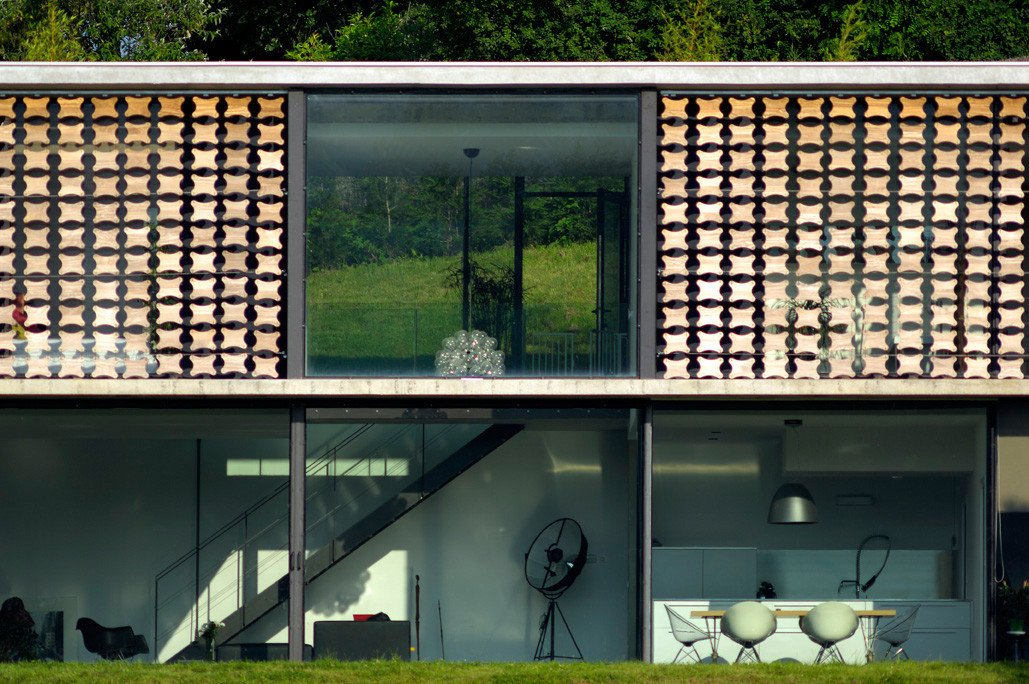 A closer look at the facade Tagged: Wood Siding Material, Windows, Concrete Siding Material, Metal Siding Material, House, Green Roof Material, Sliding Window Type, and Metal.  Biscuit House by AUM Pierre Minassian