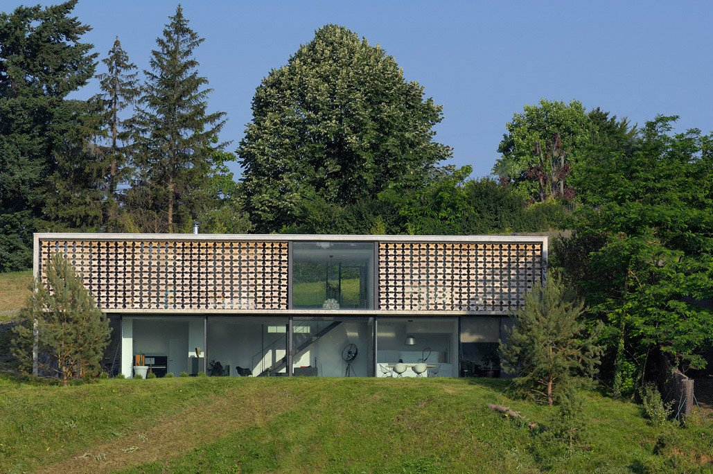 The house nestled in the forest Tagged: Concrete, Metal, Wood, House, Outdoor, Field, Shrubs, Back Yard, Slope, Woodland, Grass, and Trees.  Best Outdoor Slope Grass Photos from Biscuit House