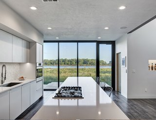 Discover 6 Amazing Riverside Homes - Photo 8 of 12 - Although the front of the house has a neatly manicured lawn, the rear of the house looks out to views of the untamed prairie. The kitchen and its floor-to-ceiling glass doors were specifically designed to allow for views from the kitchen island out to the Missouri River.