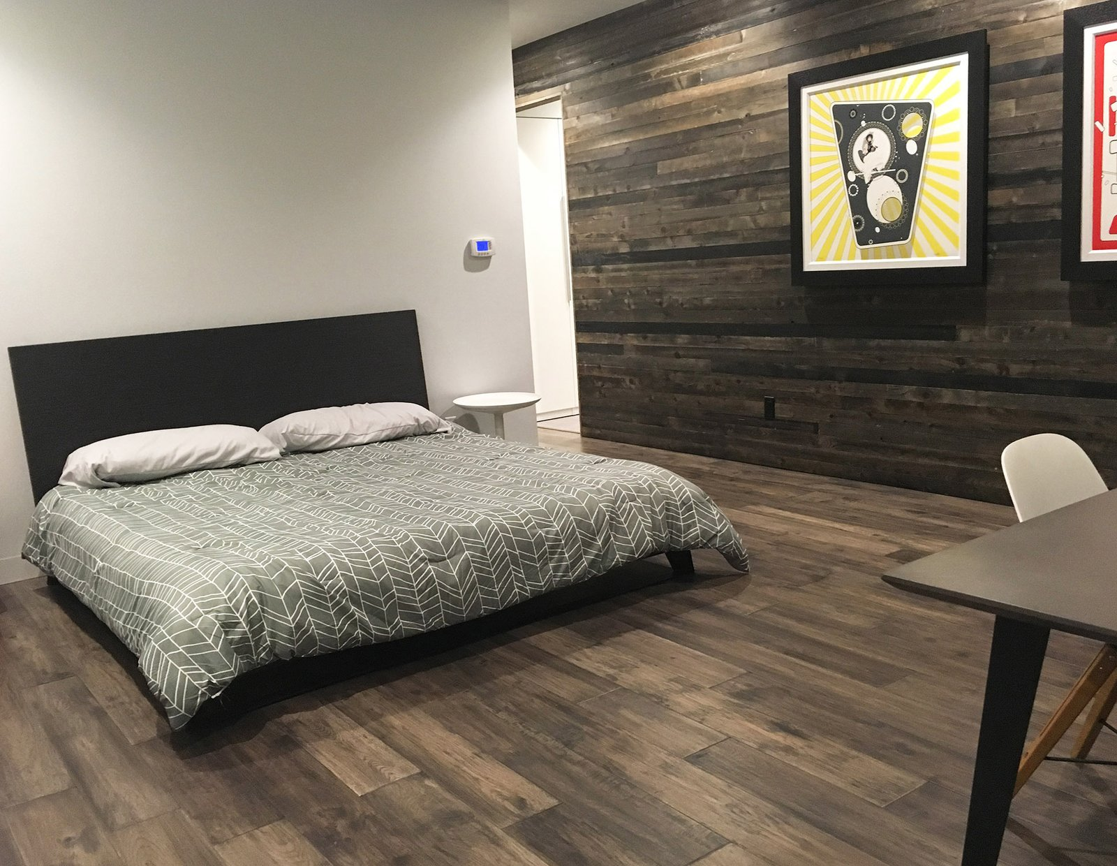 View showing the guest bedroom with the formerly-exterior cedar-sheathed wall in the background. (2017)  Tagged: Bedroom, Bed, Night Stands, Recessed Lighting, and Dark Hardwood Floor.  530 house by Nathan Kalaher