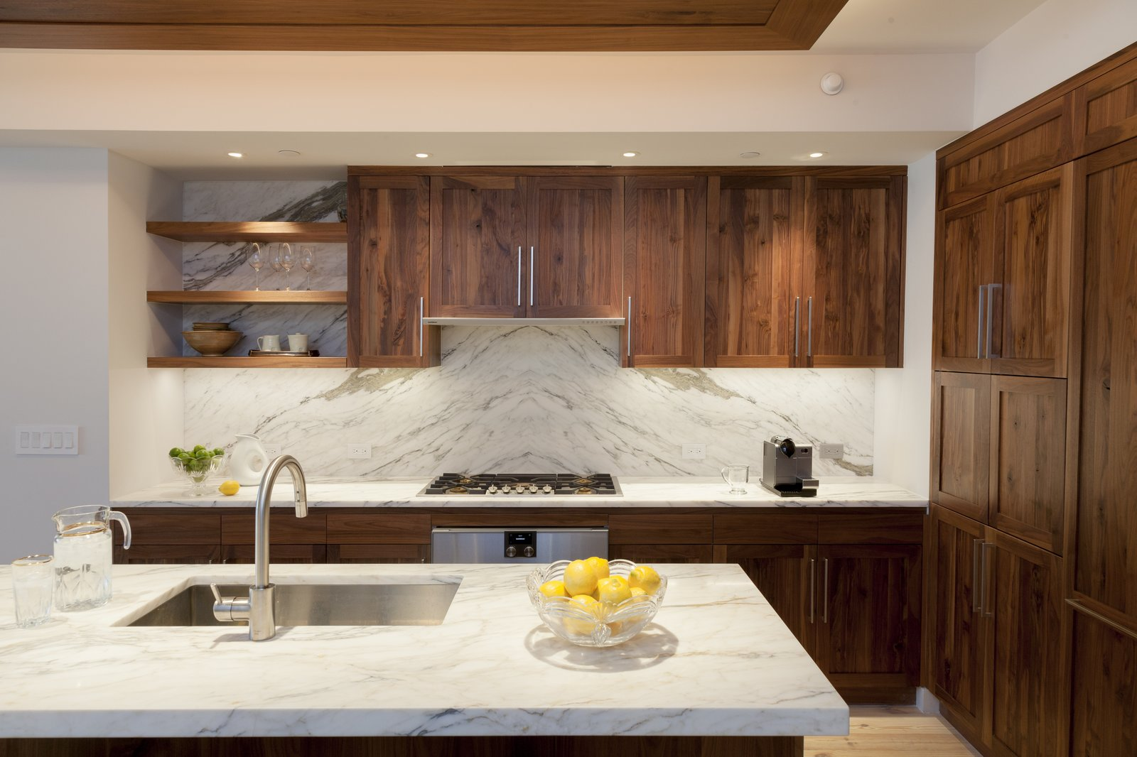 Walnut and book-matched  Calcutta kitchen Tagged: Kitchen, Marble, Wood, Stone Slab, Ceiling, Pendant, Light Hardwood, Accent, Recessed, Refrigerator, Wall Oven, Cooktops, Range, Range Hood, Wine Cooler, Ice Maker, Dishwasher, Microwave, and Undermount.  Best Kitchen Refrigerator Dishwasher Photos from Pierhouse At Brooklyn Bridge Park Condo
