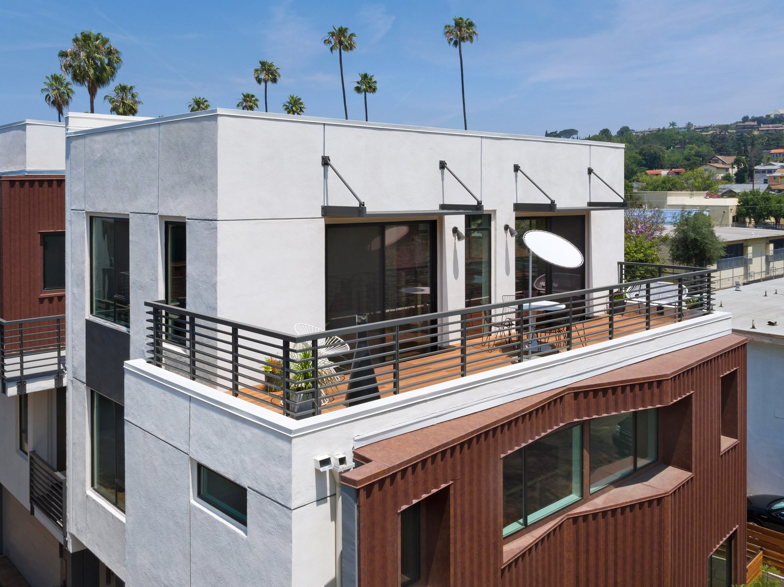 Palm trees and hillsides are among the views from large outdoor decks. Tagged: House, Stucco Siding Material, Metal Siding Material, Large Patio, Porch, Deck, Wood Patio, Porch, Deck, Concrete Patio, Porch, Deck, Metal Fences, Wall, Rooftop, Doors, Exterior, and Sliding Door Type.  COVO by KTGY Architecture + Planning