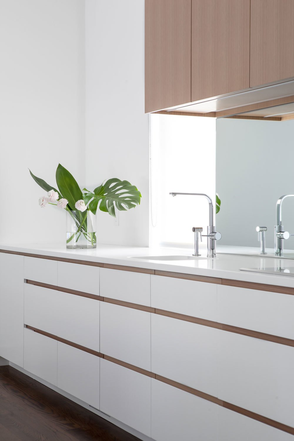 Mirrored backsplash deflects light from the opposite window and softens a typically, hard, utilitarian surface. Tagged: Kitchen, Quartzite, White, Wood, Light Hardwood, Mirror, Recessed, Undermount, and Medium Hardwood.  Best Kitchen Medium Hardwood Mirror Photos from Coach House