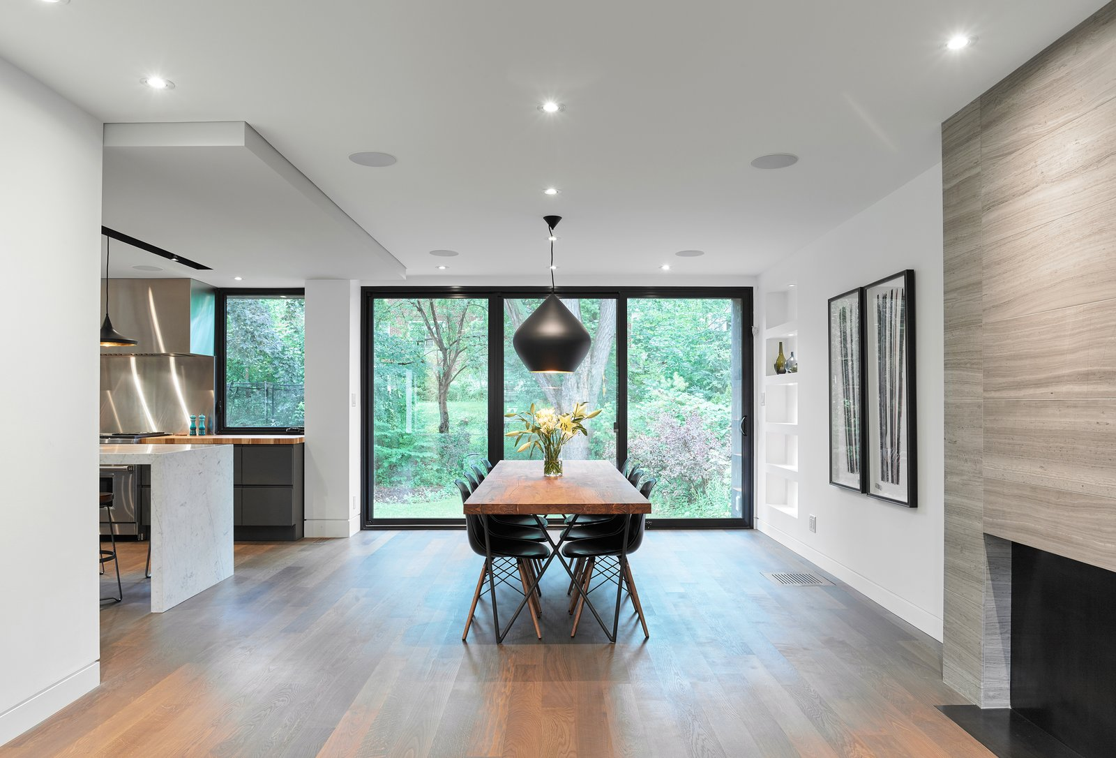 Tagged: Dining Room, Standard Layout Fireplace, Pendant Lighting, Table, Wood Burning Fireplace, Medium Hardwood Floor, Chair, Shelves, and Recessed Lighting.  Hibou House by Barbora Vokac Taylor Architect