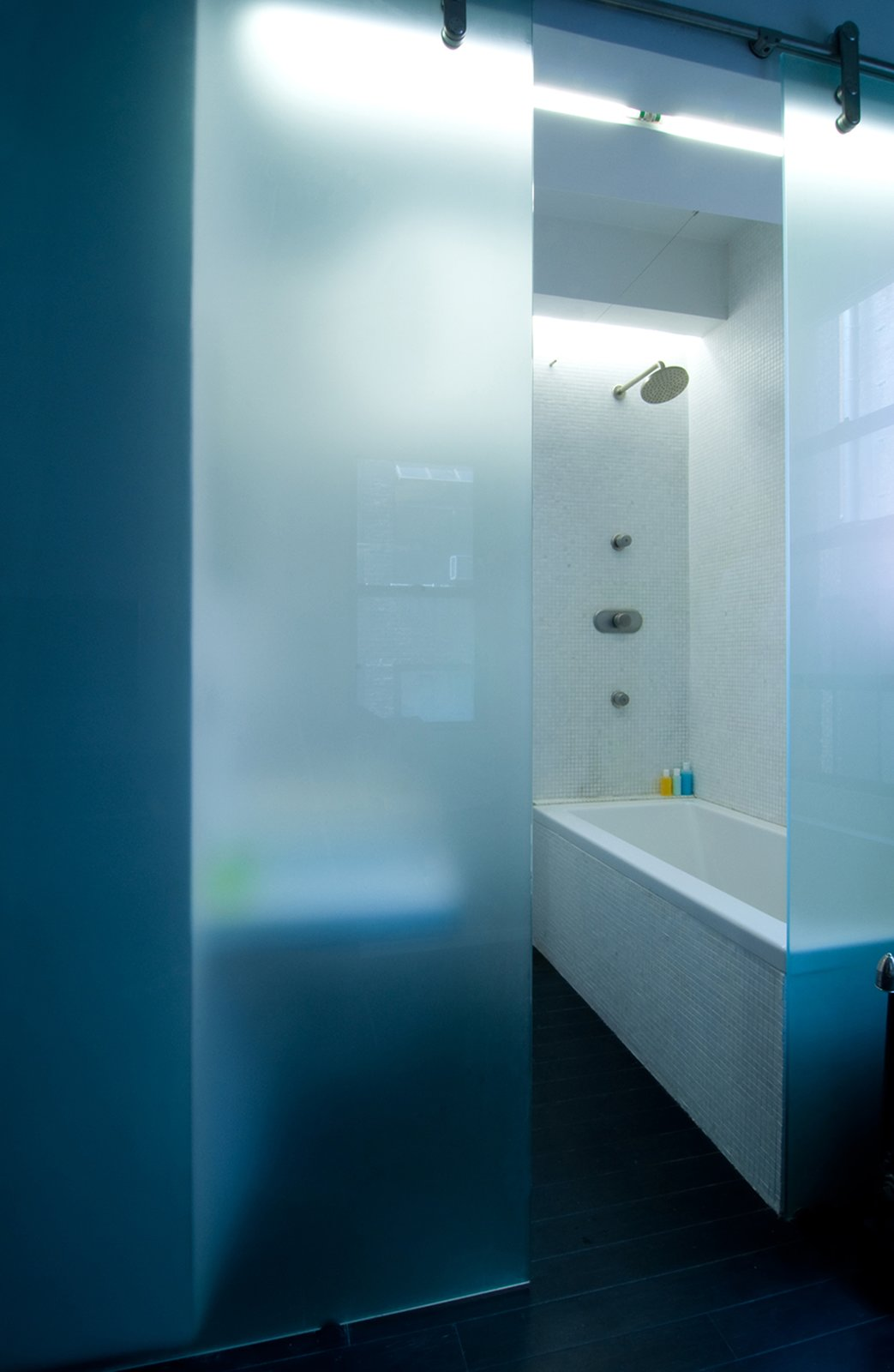 Acid-etched frosted, barn style- sliding glass panel Tagged: Bath Room, Drop In Tub, Open Shower, and Mosaic Tile Wall.  Park Avenue Studio by Ajay Chopra