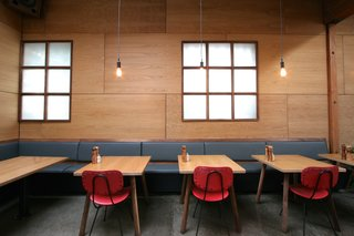 An Australian Cafe Filled With Handcrafted Details Comes to Portland, Oregon - Photo 3 of 7 - Red chairs lend a pop of color against rich oak walls and walnut-and-leather banquets.