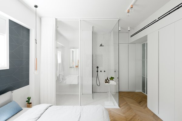 Master bed room overlooking en-suit classic-European style bathroom sectioned off with a curtain for privacy.
