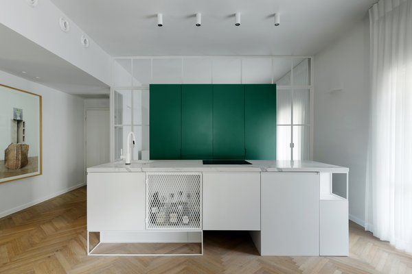 "kitchen- green cube storage containing two refrigerators inside, a water bar, a coffee machine as well as dishes and food supply. The cube was then ""wrapped around"" by a  glass vitrine divided by stone-white colored Belgium profiles with  two entries one on each side of the cube leading to a  family-room."