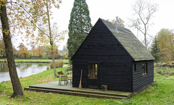 London-based practice De Rosee Sa's self-built lakeside cabin recaptures the magic of childhood fairytales.   A labor of love, the 377-square-foot Woodland Cabin is a design/build project completed over multiple trips to the lakeside lot in the village of Nouvelles in southern Belgium. The architects built the cabin using locally-sourced, storm-felled timber to deepen their understanding of materials and construction.   By taking construction into their own hands and using locally-sourced materials, the team kept within the relatively tight budget of £25,000 ($32,872).    Simple yet elegant, De Rosee Sa's self-described