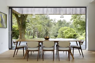 50 Modern Homes With Floor-to-Ceiling Windows - Photo 34 of 50 - London-based architecture and design studio Alma-nac designed House in the Woods, a contemporary home surrounded by pristine forest in England's South Downs National Park to replace a decrepit, 1950s bungalow. The new 240-square-meter dwelling retains the former building's simple gabled form and footprint, but offers greater flexibility with its ability to change from a single bedroom home to five bedrooms for large family gatherings.