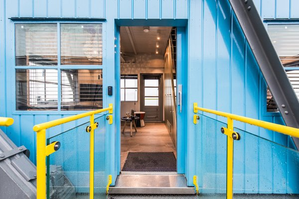 The repurposed metal containers are painted bright blue.