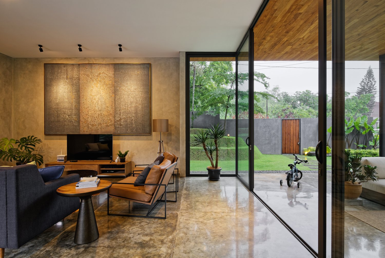Raw concrete walls and polished concrete floors are used in the interior to form a neutral backdrop for built-in wood furniture and colorful rugs and artworks.