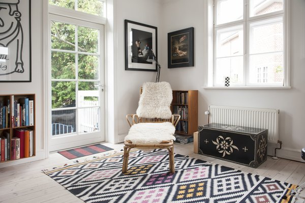 Bamboo chair with fur throws sits atop yellow, pink, and black diamond patterned rug near a black antique chest.