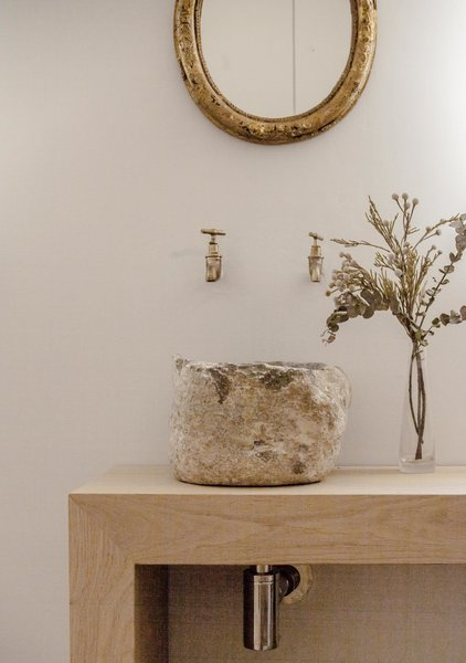 In the main bedroom there is a bespoke vanity in oak with a basin crafted from locally sourced stone