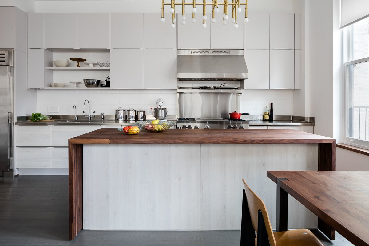 The kitchen features an industrial range and stainless steel counters. Tagged: Kitchen, Range, Range Hood, Metal Counter, and Subway Tile Backsplashe.  Best Photos from 5th Avenue Apartment
