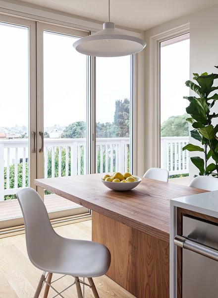 Floor to ceiling windows brighten the small footprint. Custom elm wood table by Kaimade.
