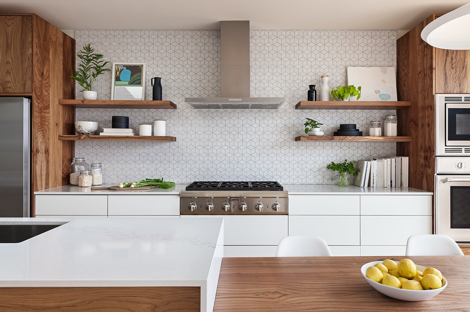 The Heath Ceramics wall tile backsplash was extended to full height and behind floating shelves to add texture and character to the minimal kitchen. Tagged: Kitchen, Refrigerator, Wall Oven, Range, Range Hood, Engineered Quartz, White, Wood, Laminate, Ceramic Tile, Pendant, Recessed, and Undermount.  Best Kitchen Engineered Quartz Undermount Photos from Los Palmos