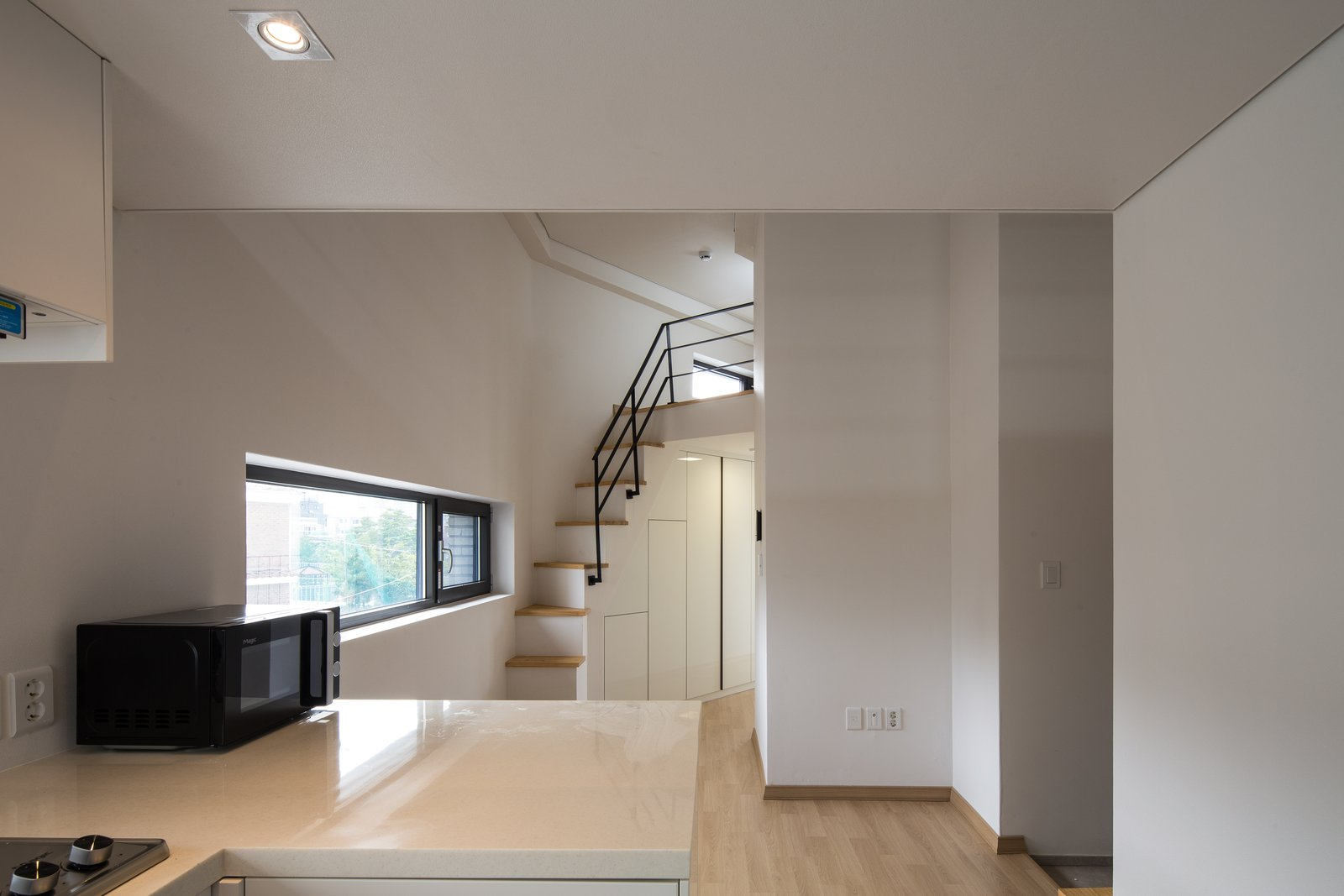 Attic stair Tagged: Living Room, Bar, Ceiling Lighting, and Light Hardwood Floor.  Best Photos from Micro Housing K