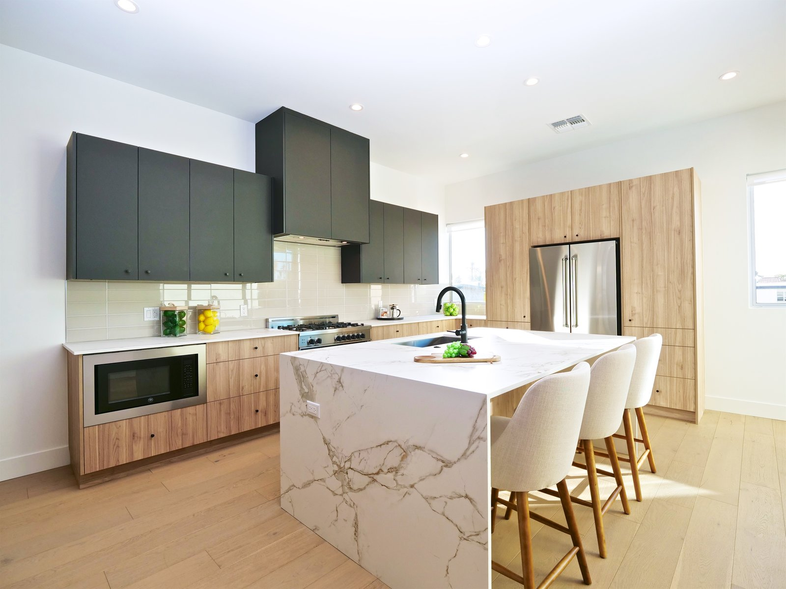 Silestone Dekton countertops, a waterfall island and Bertazzoni appliance package.  Tagged: Kitchen, Medium Hardwood Floor, Ceiling Lighting, Refrigerator, Range, Microwave, Engineered Quartz Counter, Wood Cabinet, Undermount Sink, and Dishwasher.  Stacks Modern by Chris Morrison