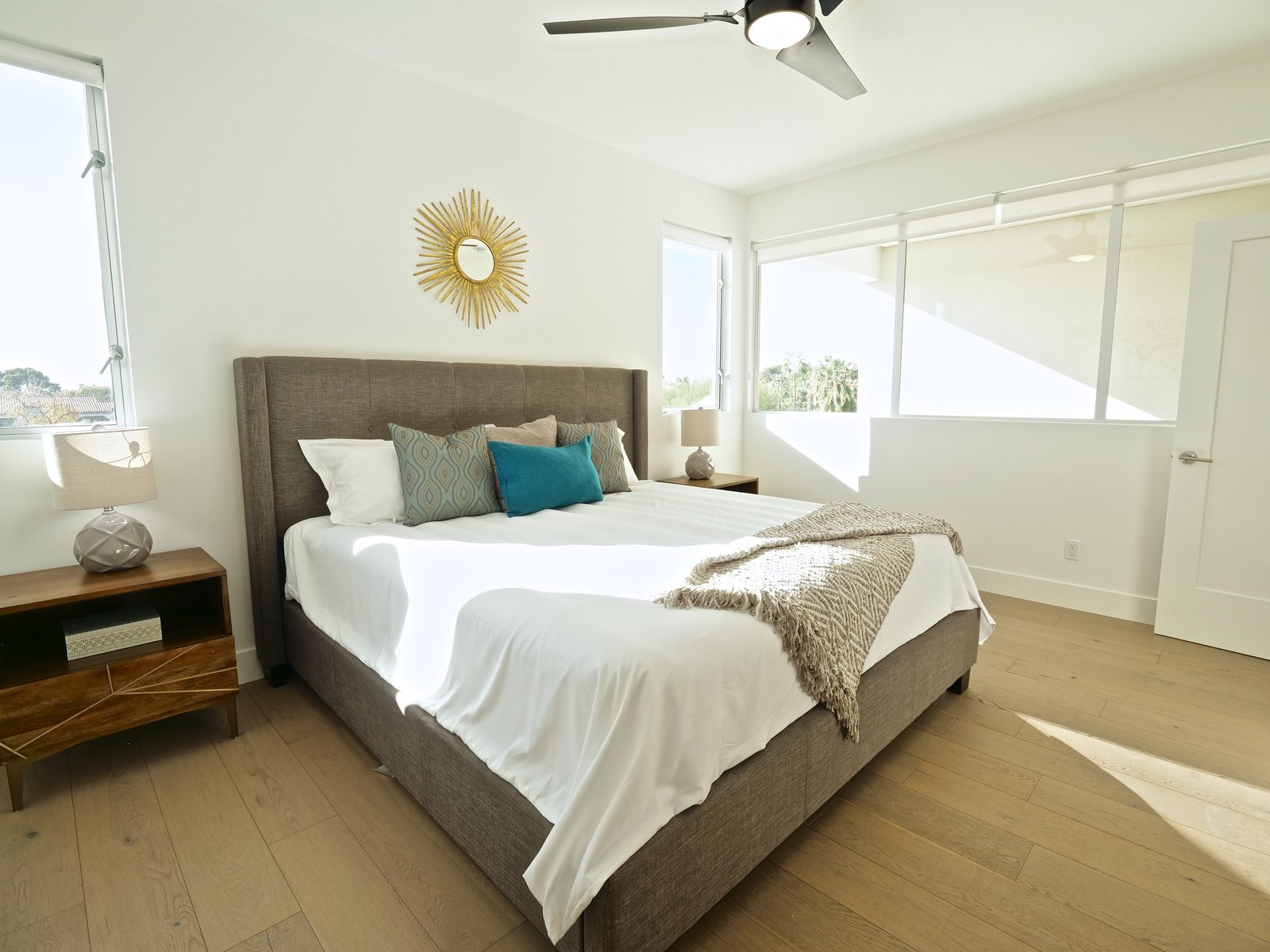 Master suite with ample natural light and en suite bath. Tagged: Bedroom, Dresser, Bed, Ceiling Lighting, Medium Hardwood Floor, Night Stands, and Table Lighting.  Stacks Modern by Chris Morrison