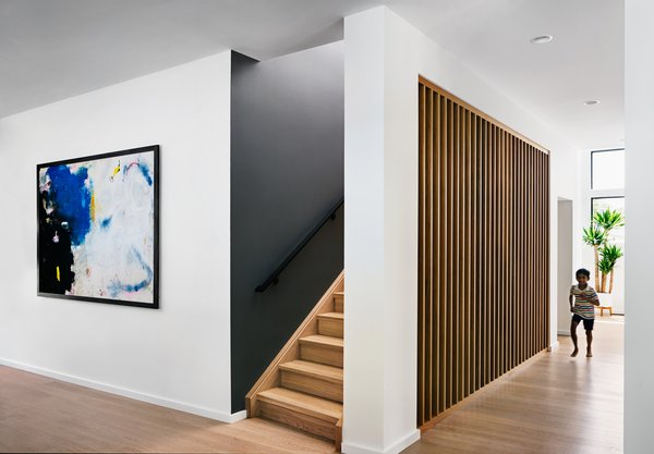 Stairway with custom slat wall to give a hint of the stair beyond, while eliminating the need for extravagant, unwanted visual clutter of a railing.