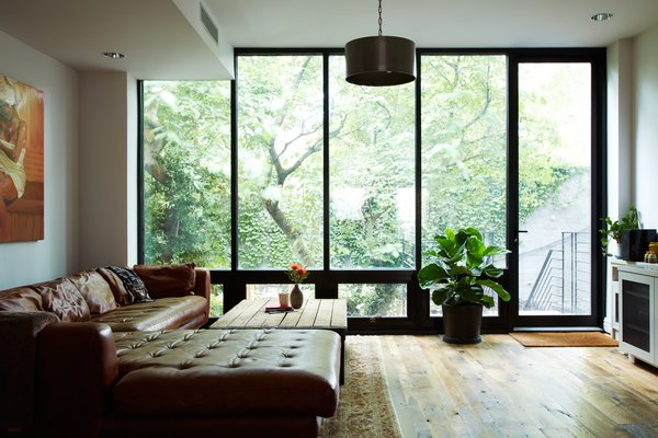 The rearwall was engineered with a large steel lintel, allowing for a full window wall.  The result is a light-filled living space that feels part of the garden.