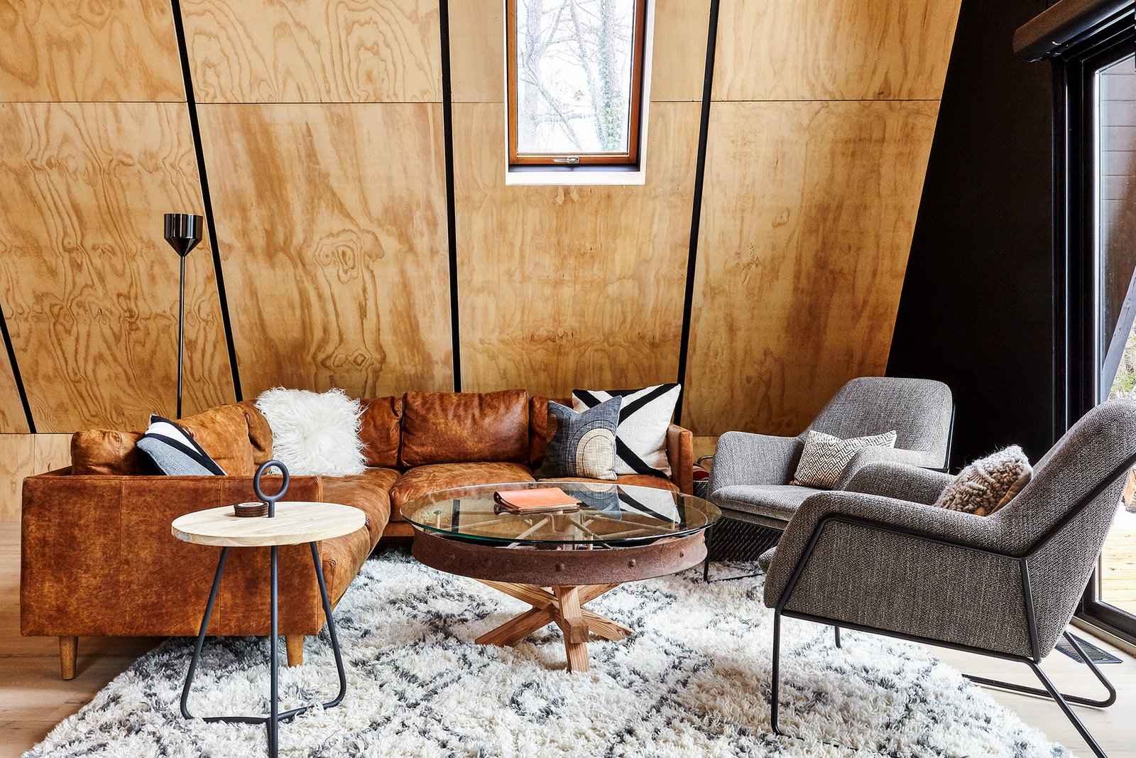 Living room with furnishings by Article & custom wagon wheel table by Ovuud