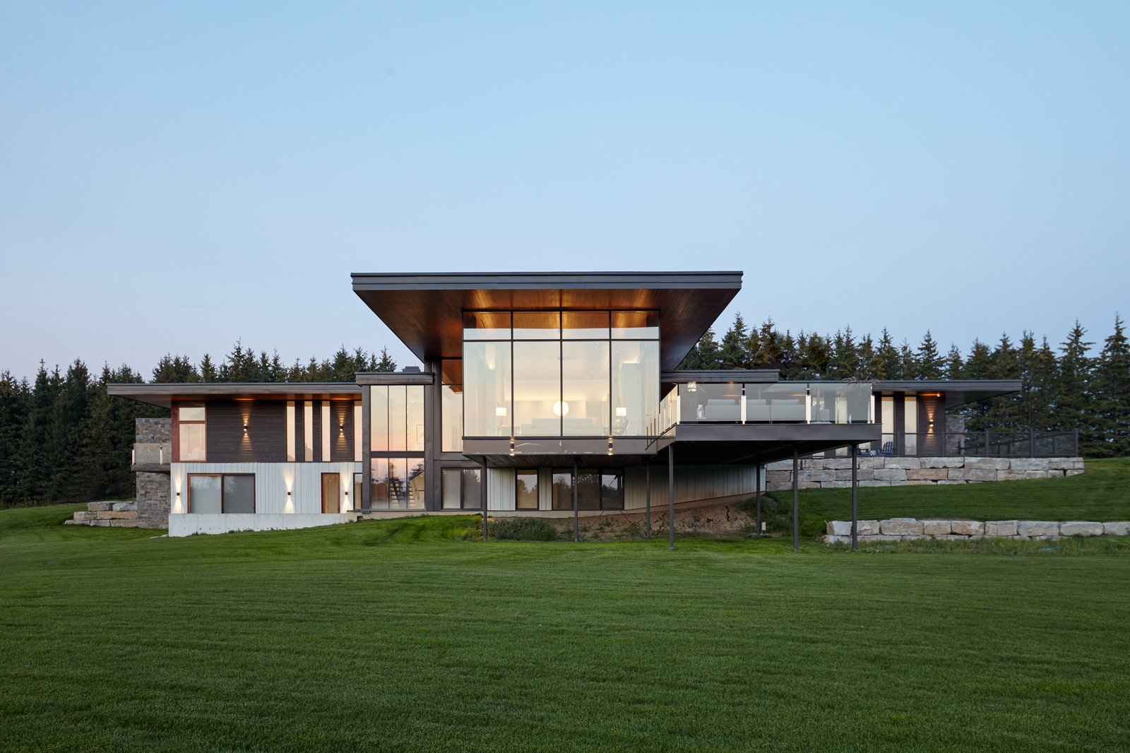 Rear view onto vast landscape with strong lines, custom curtain wall and large overhangs to protect form the sunlight