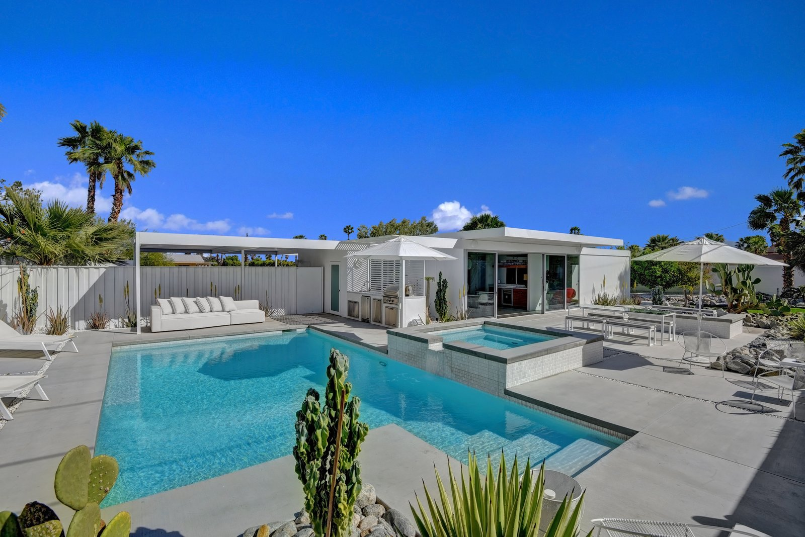Facing east from pool and spa to outdoor kitchen and house.
