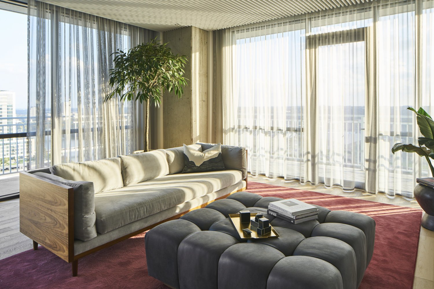 Living Room with wraparound balcony, cement walls, bubble tufted ottoman, wooden couch base, sheer curtains and red area rug.