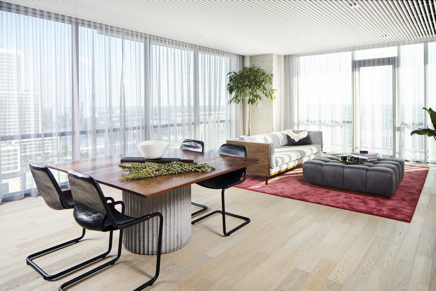 Modern living room with leather sling chair, walnut frame sofa, and wooden tabletop with a concrete base.