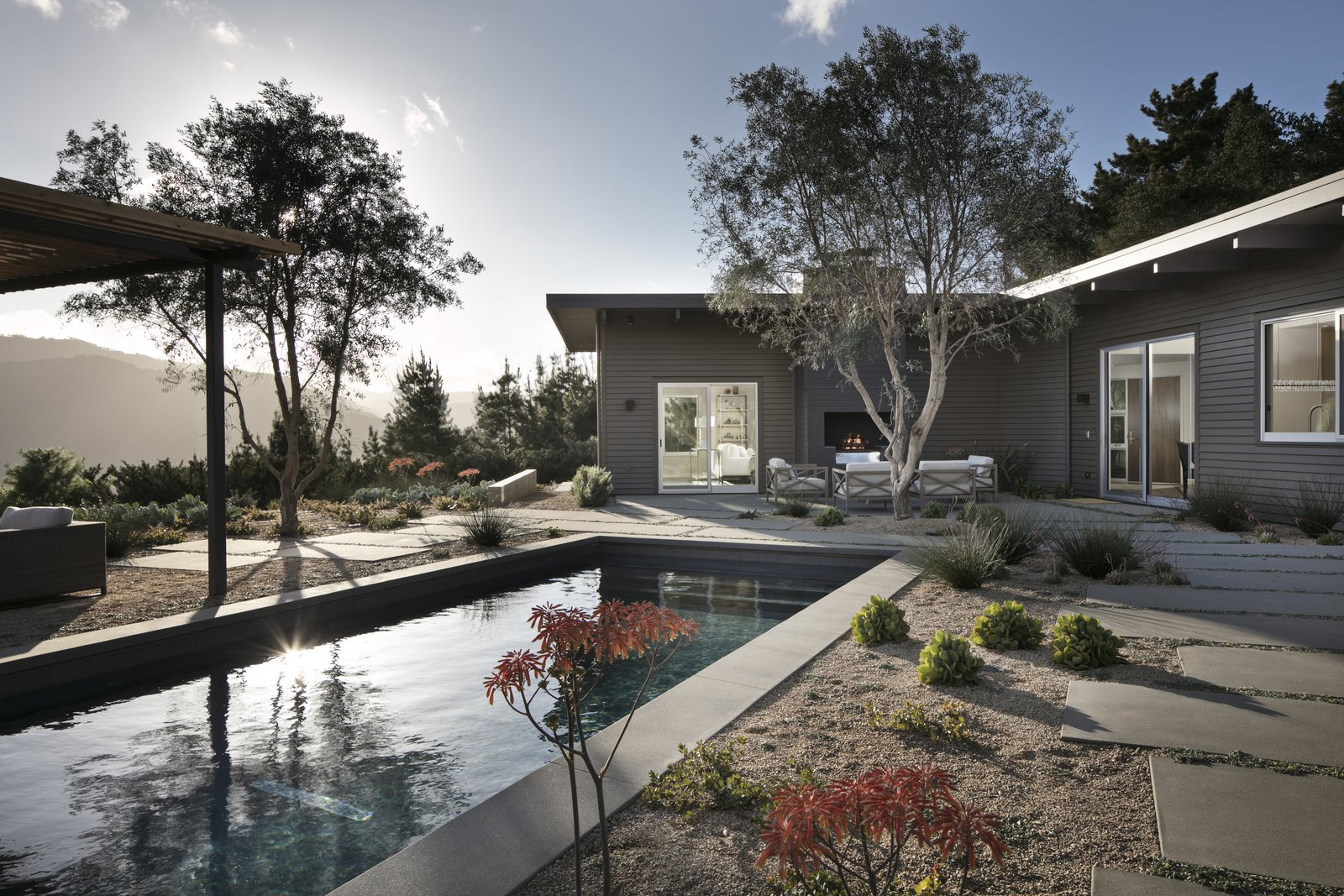 Backyard and outdoor living spaces, looking over the pool to the home and mountain views