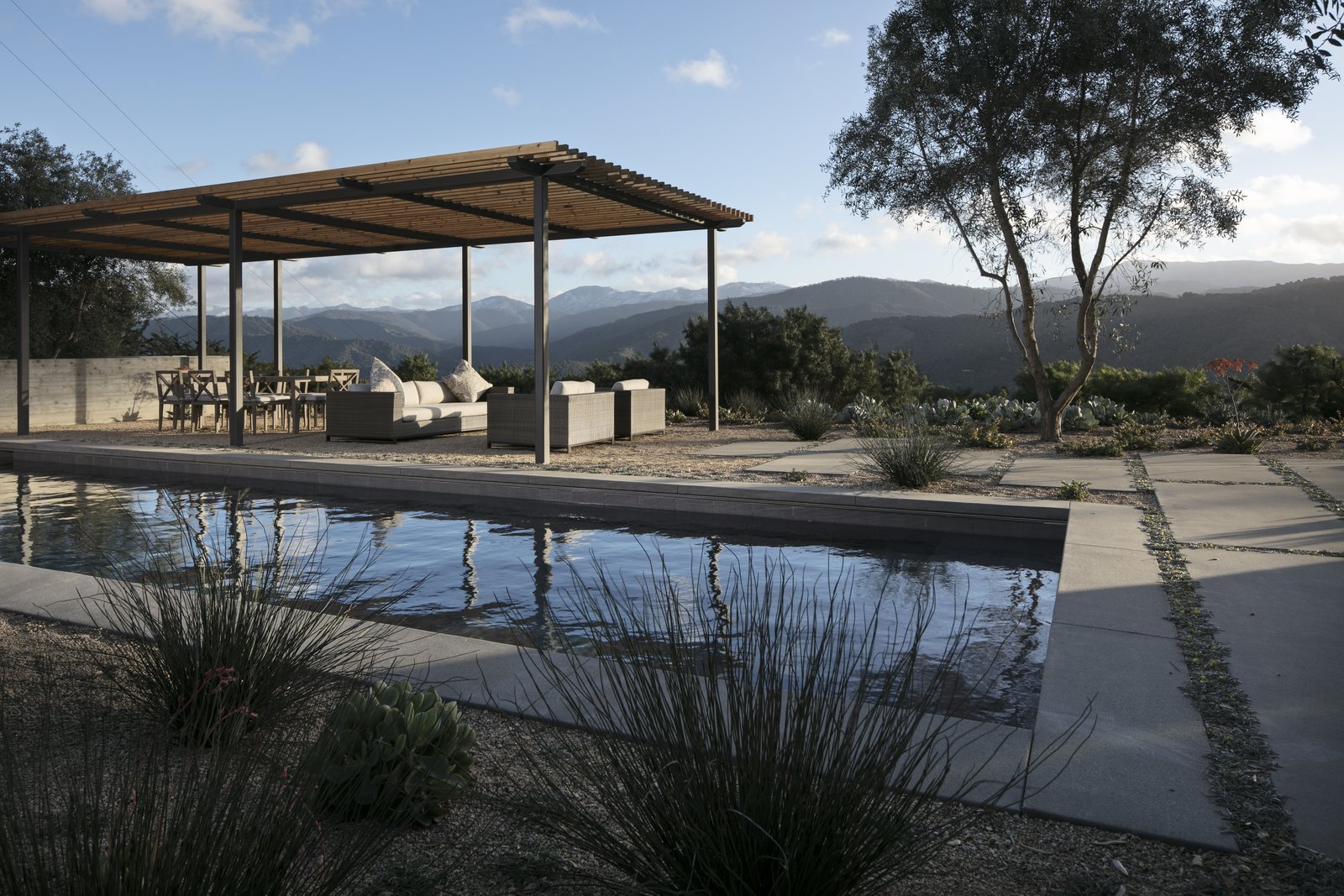 Looking over the pool to the outdoor living room and mountain views.